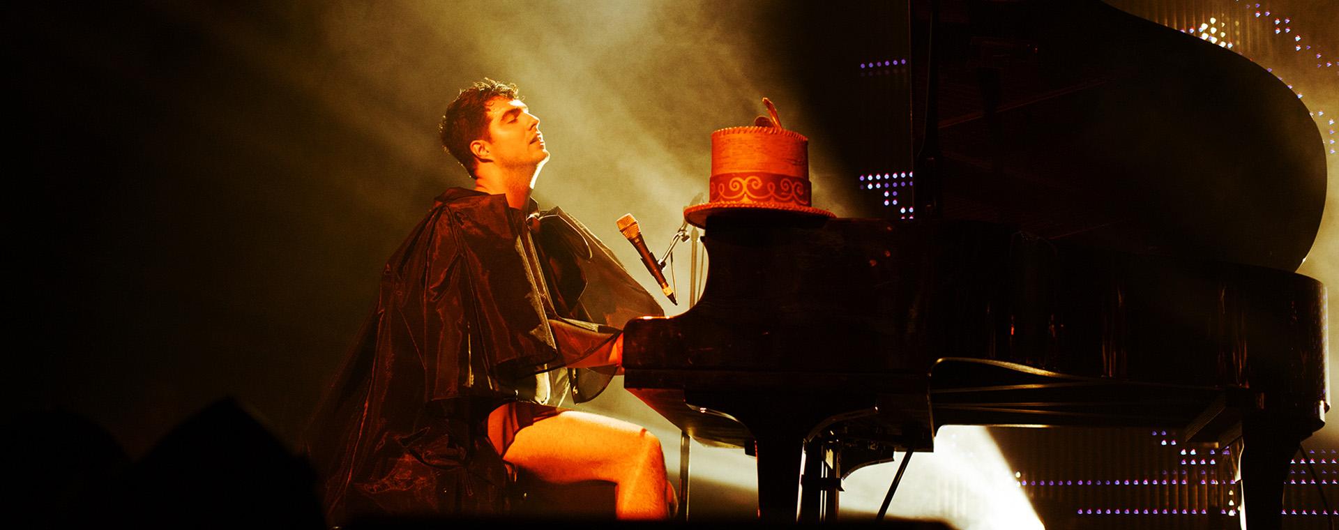 Un homme vêtu d'une cape est assis au piano. Son chapeau haut de forme est posé sur le piano. Ses yeux sont fermés.