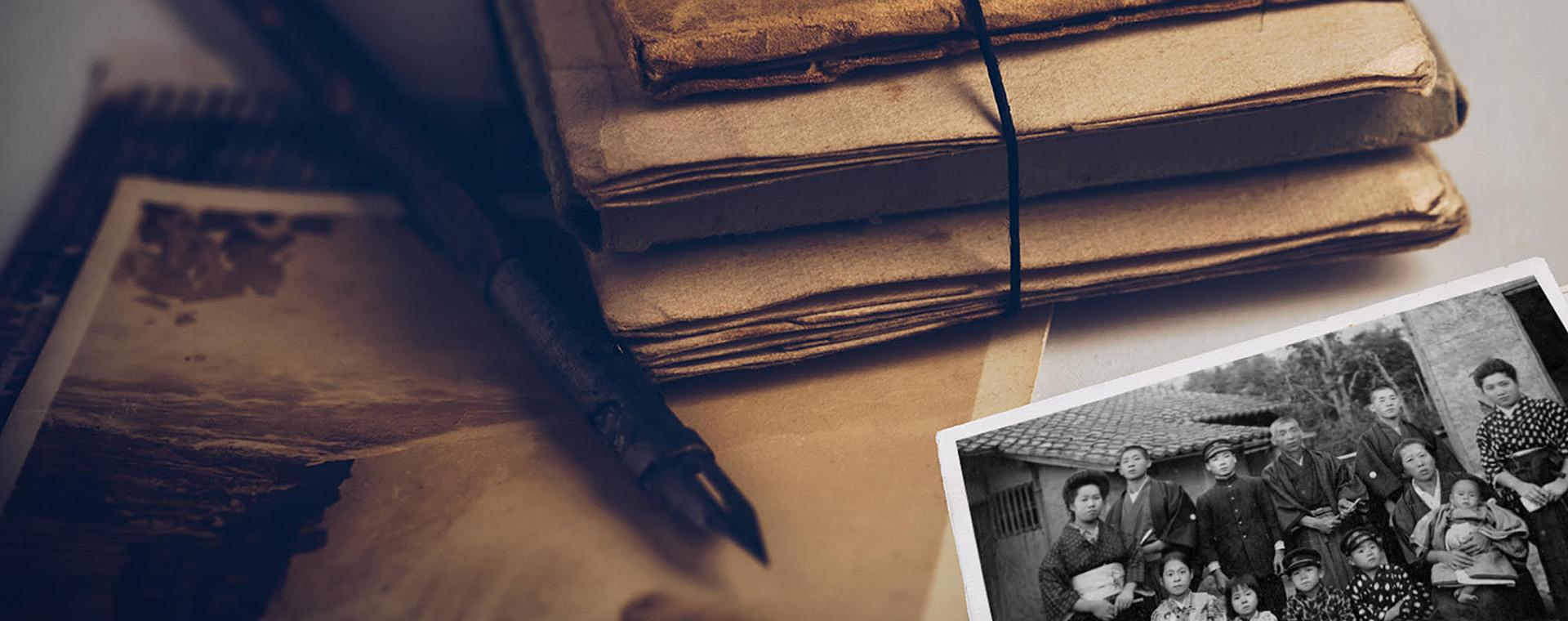 Un paquet de documents aux tons sépia sur un bureau avec un album aux tons sépia et une photo en noir et blanc de personnes